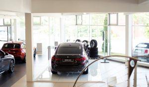 Ein schwarzes Auto in einem Autohaus, welches in der Mitte steht, umgeben von anderen Autos. Vor dem schwarzen Auto sind gestapelte Reifen zu erkennen.