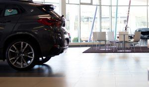 Ein Bildausschnitt aus einem Autohaus bei dem eine Sitzecke und ein graues Auto zu erkennen ist.