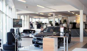 Ein Bild einer Präsentationsfläche des Autohaus Müllers mit einem schwarzen BMW in der Mitte und Reifen auf der linken Bildseite. Im Hintergrund sieht man entschärft eine Bürofläche mit Angestellten des Autohauses.