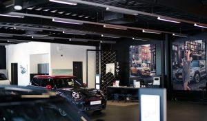 Ein MINI Auto Verkaufsbereich, welcher dunkel gehalten ist. Des Weiteren sind zwei große Bilder von MINIs auf der dunklen Wand zu erkennen und ein ausgestellter MINI John Cooper Works.