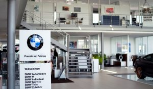 """Ein Bild von einer Eingangshalle eines Autohauses, auf der linken Seite ist ein Aufsteller von BMW zu sehen mit dem Logo und Slogan """"Freude am Fahren"""" darunter sind die Angebote des Autohauses aufgelistet."""
