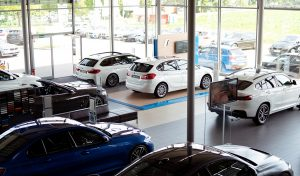 Eine von oben fotografierte Präsentationsfläche eines Autohauses auf dem sechs BMW-Modelle stehen, durch die Glasfront des Autohauses sieht man weitere Autos, die auf der Außenfläche geparkt sind.
