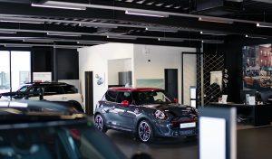 Ein Bildausschnitt einer Präsentationsfläche eines Autohauses, im Fokus steht sportlicher MINI Cooper in grau mit rotem Dach und Außenspiegel.
