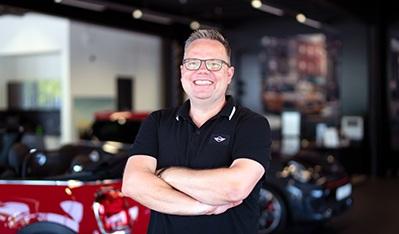 Ein Bild von Alexander Berndt in einem MINI Autohaus. Er hat hierbei die Arme verschränkt und lächelt.