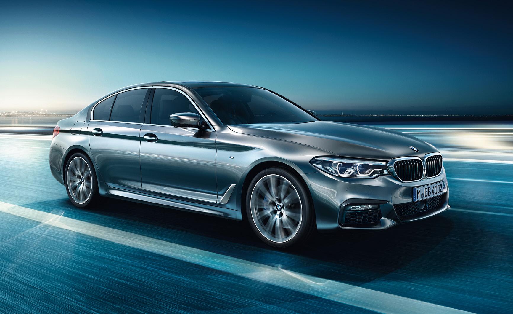Ein grauer 5er BMW der auf einer Straße fährt. Im Hintergrund erkennt man Wasser und Lichter.
