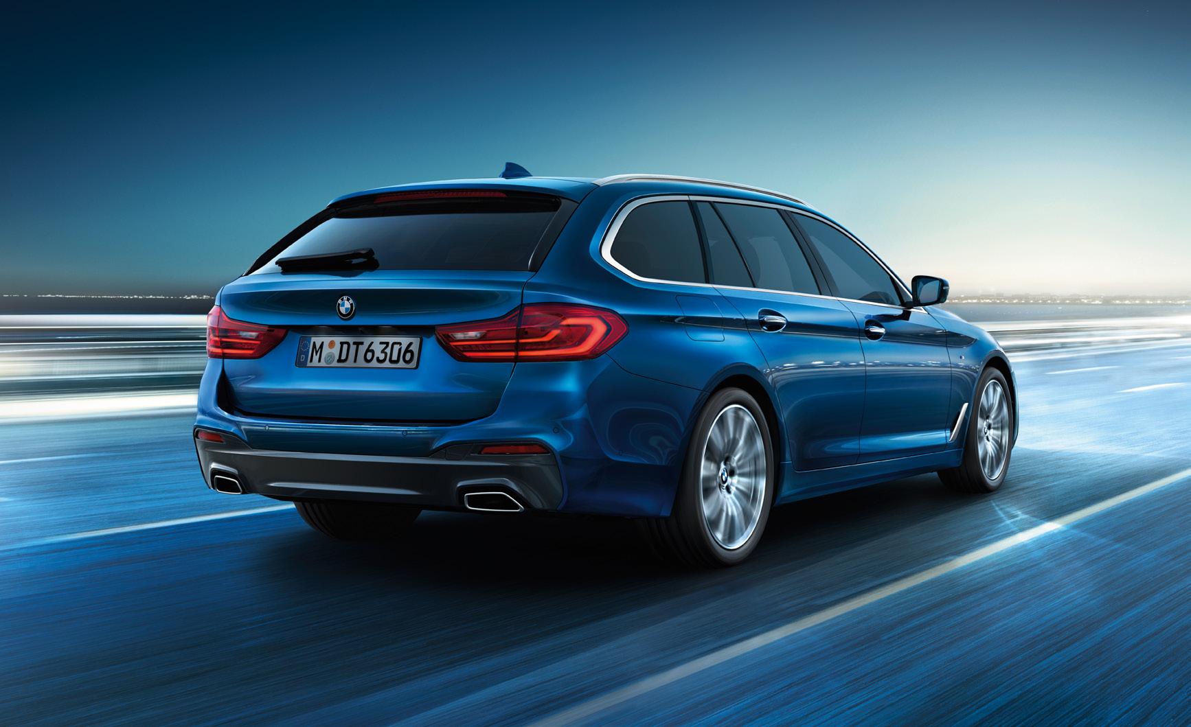 Ein blauer, von hinten fotografierter 5er BMW der auf einer Straße fährt. Der Fokus liegt hier auf dem Auto und der Hintergrund ist sehr verschwommen.